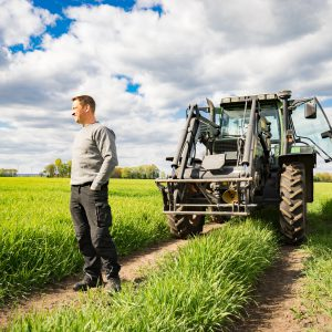 Landwirt mit Traktor im Getreidefeld - unternehmerische Freiheit und Zukunftssorgen